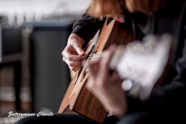 zdjęcie; zbliżenie na ręce dziewczyny grającej na gitarze klasycznej