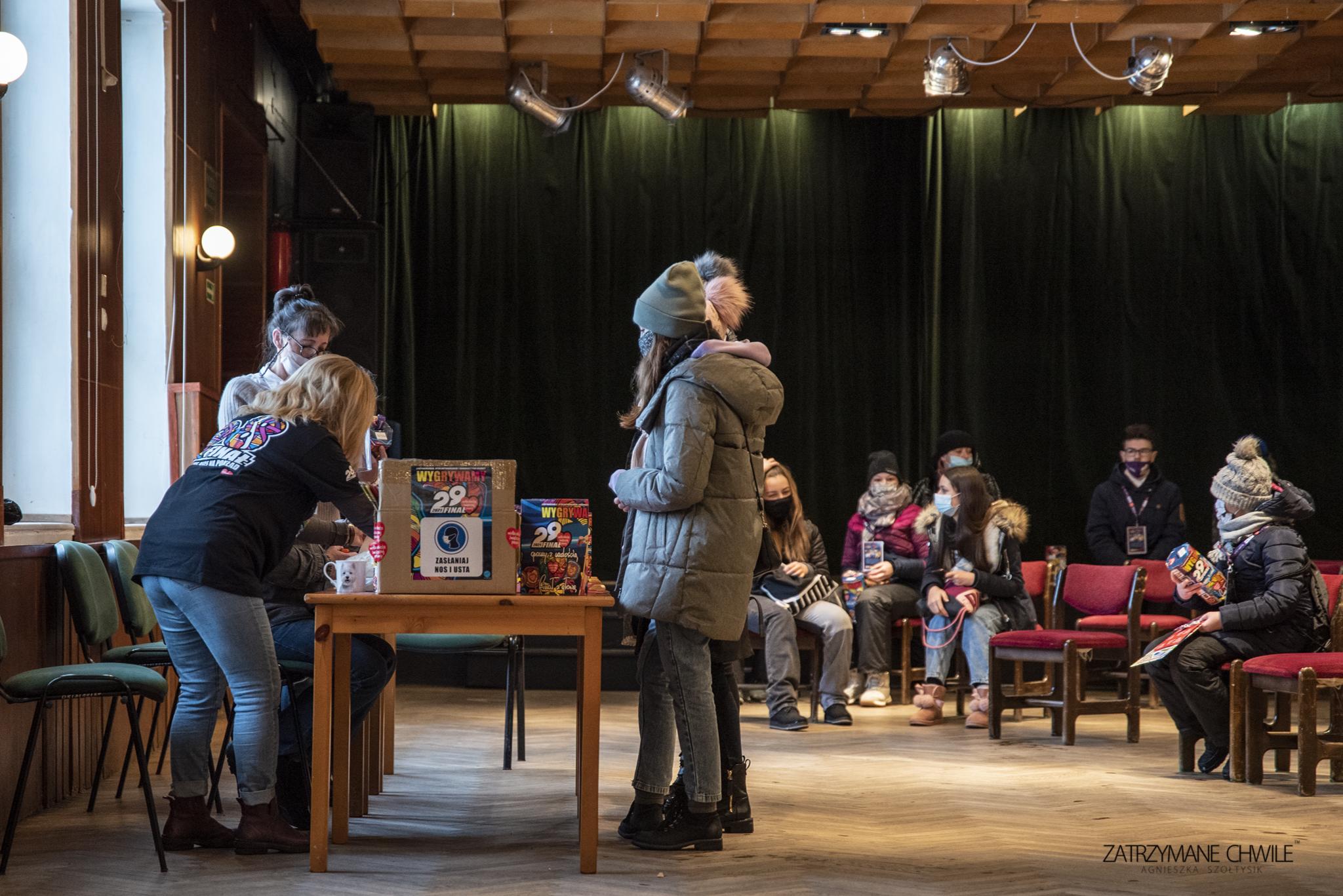 zdjęcie; duża sala z reflektorami, stoły i krzesła, trzy osoby dorosłe wydają 2 wolontariuszkom WOŚP puszki i kominy, na krzesłach siedzi 6 ludzi w maseczkach i czeka