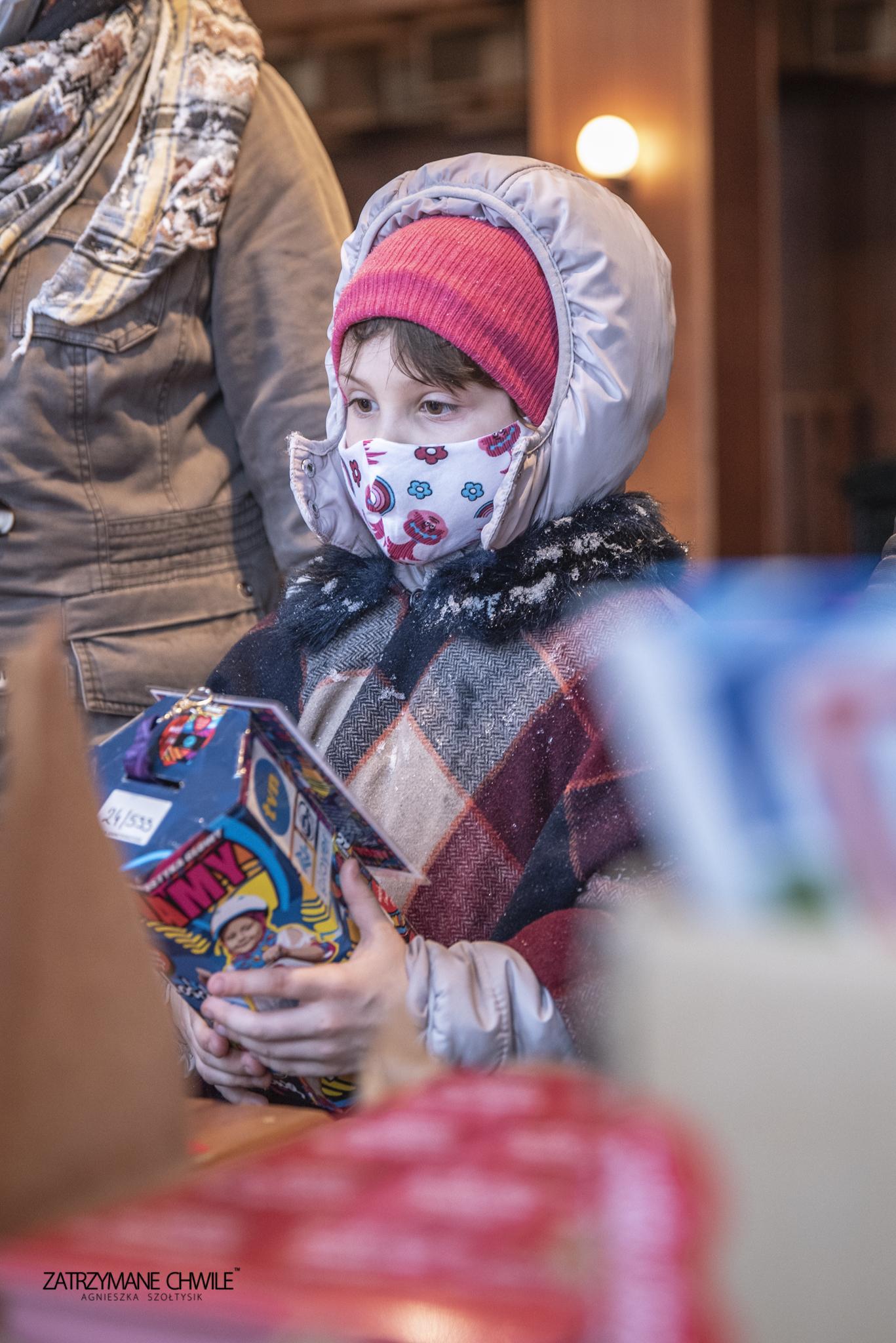 zdjęcia; mała dziewczynka ubrana na zimowo trzyma w ręku puszkę WOŚP, obok niej stoi kobieta, której nie widać twarzy