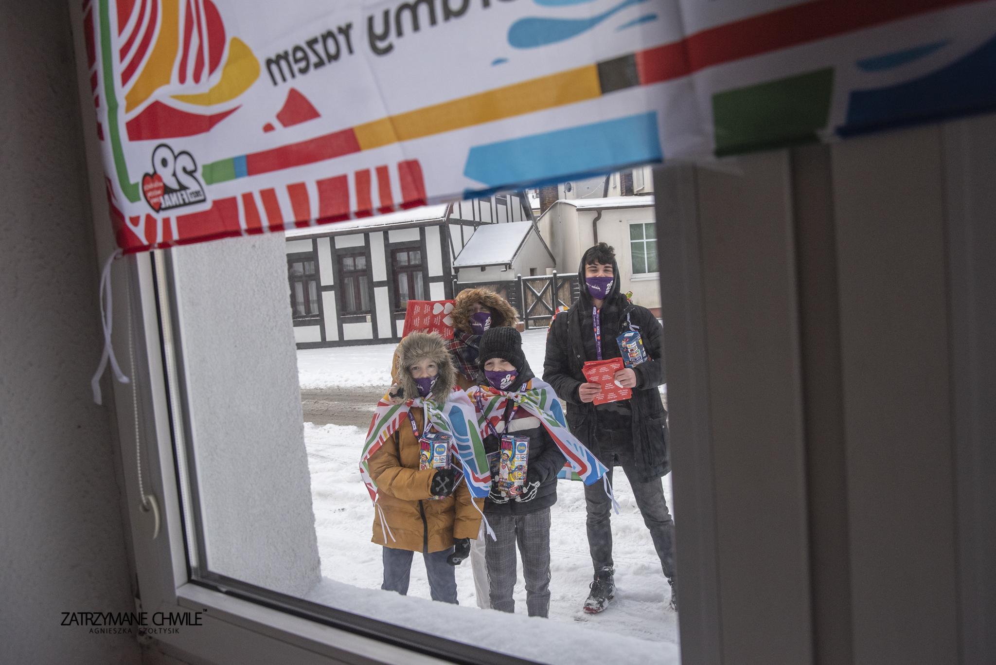 zdjęcie; za oknem widać wolontariuszy z puszkami WOŚP (dwójkę dzieci i dwóch nastolatków), ubrania zimowe, dzieci mają założone na siebie flagi 29. Finału
