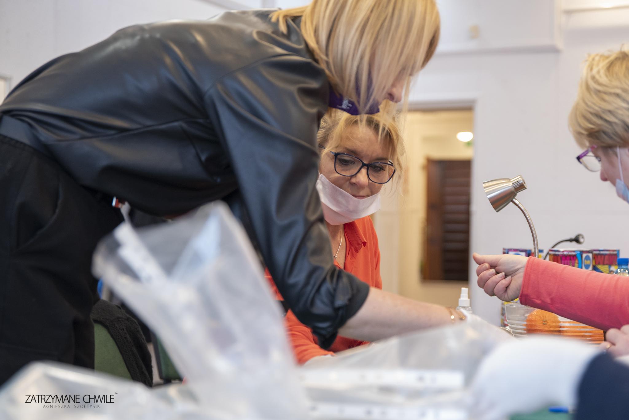 zdjęcie; kobieta w czerni nachyla się nad stołem i liczy pieniądze obok i na przeciw niej dwie kobiety siedzące liczą pieniądze na WOŚP