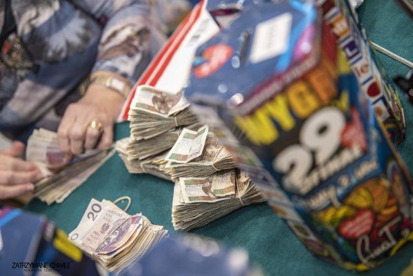 zdjęcie; puszka WOŚP, pieniądze, ręce kobiety która liczy plik banknotów