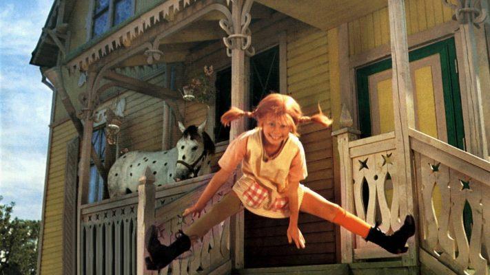 kadr z filmu, Pippi skacze w rozkroku na tle Willi Śmiesznotki, na ganku stoi koń